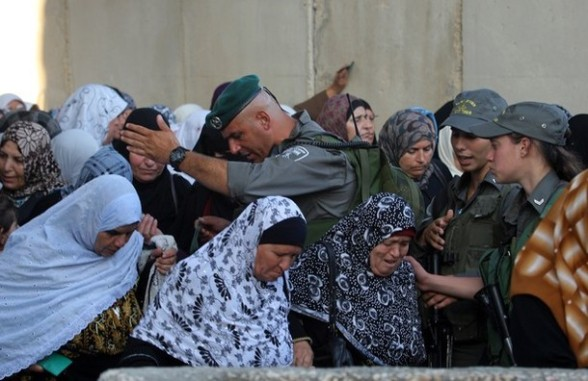 Israeli border police allow Palestinian women to cross into Jerusalem from the West Bank city of Bethlehem after checking their ID cards on July 27, 2012. Palestinian Muslims are heading to Jerusalem to attend the second Friday prayers of the fasting month of Ramadan at the Al-Aqsa mosque compound. AFP PHOTO / MUSA AL-SHAER