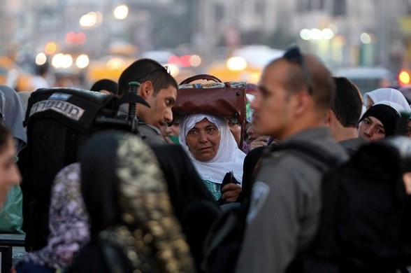 A Palestinian woman waits to be given permission by Israeli border policemen to cross into Jerusalem at the Qalandia checkpoint near the West Bank city of Ramallah on July 27, 2012. Palestinian Muslims are heading to Jerusalem to attend the second Friday prayers of the fasting month of Ramadan at the Al-Aqsa mosque compound. AFP PHOTO / ABBAS MOMANI