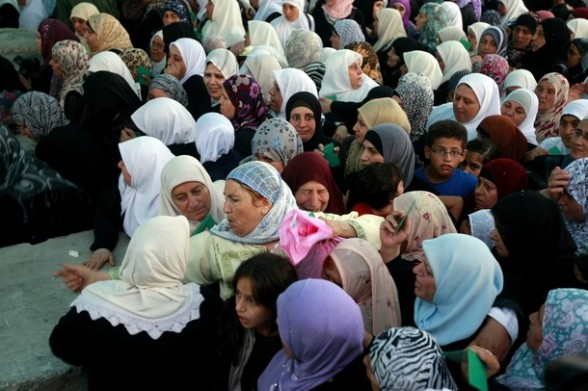 Palestinian women waiting to cross through an Israeli checkpoint on their way to pray at the Al-Aqsa Mosque in Jerusalem, on the second Friday off the Muslim holy month of Ramadan near the West Bank city of Ramallah, Friday, July 27, 2012. Ramadan is the ninth month of the Muslim year which lasts 30 days, during which strict fasting is observed from sunrise to sunset. (AP Photo/Majdi Mohammed)
