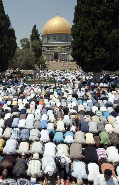 Palestinian worshipers pray outside the Dome of the Rock at the al-Aqsa mosque compound in Jerusalem during the second Friday prayers of the Muslim holy month of Ramadan on July 27, 2012. Muslims fasting in the month of Ramadan must abstain from food, drink and sex from dawn until sunset, when they break the fast with the meal known as Iftar. AFP PHOTO/AHMAD GHARABLI