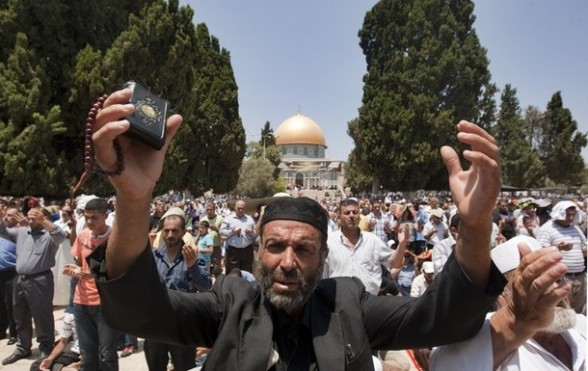 A Palestinian worshiper holding a Koran, Islam's holy book, and prayer beads, prays outside the Dome of the Rock at the al-Aqsa mosque compound, in Jerusalem, during the second Friday prayers of the Muslim holy month of Ramadan on July 27, 2012. Muslims fasting in the month of Ramadan must abstain from food, drink and sex from dawn until sunset, when they break the fast with the meal known as Iftar. AFP PHOTO/AHMAD GHARABLI