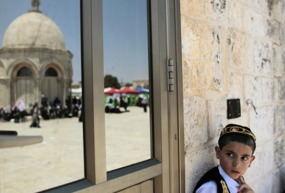 A Palestinian boy stands near the reflection of a shrine on the compound known to Muslims as Noble Sanctuary and to Jews as Temple Mount in Jerusalem's Old City on the second Friday of the holy month of Ramadan July 27, 2012. REUTERS/Ammar Awad