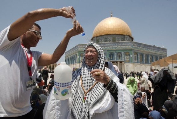 A Palestinian man pours water over a Muslim female worshiper as others pray outside the Dome of the Rock at the al-Aqsa mosque compound, in Jerusalem, during the second Friday prayers of the Muslim holy month of Ramadan on July 27, 2012. Muslims fasting in the month of Ramadan must abstain from food, drink and sex from dawn until sunset, when they break the fast with the meal known as Iftar. AFP PHOTO/AHMAD GHARABLI