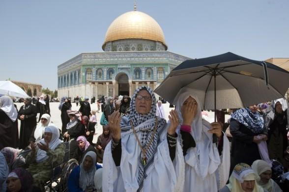 Palestinian Muslim women pray outside the Dome of the Rock at the al-Aqsa mosque compound in Jerusalem during the second Friday prayers of the Muslim holy month of Ramadan on July 27, 2012. Muslims fasting in the month of Ramadan must abstain from food, drink and sex from dawn until sunset, when they break the fast with the meal known as Iftar. AFP PHOTO/AHMAD GHARABLI