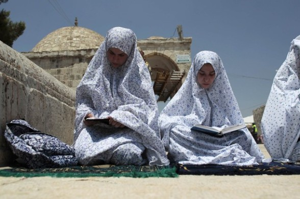 Palestinian women read the Koran on the compound known to Muslims as Noble Sanctuary and to Jews as Temple Mount in Jerusalem's Old City on the second Friday of the holy month of Ramadan July 27, 2012. REUTERS/Ammar Awad