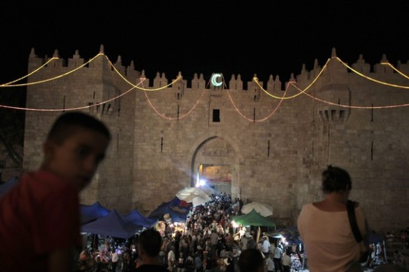 People walk through Damascus gate of Jerusalem's Old City as it is decorated for the holy month of Ramadan July 25, 2012. REUTERS/Ammar Awad