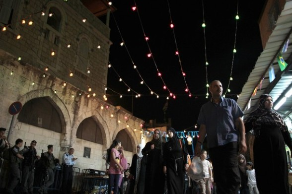 People walk in an alley decorated for the holy month of Ramadan in Jerusalem's Old City July 25, 2012.  REUTERS/Ammar Awad
