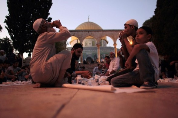 Palestinians eat donated food at the compound of the Dome of the Rock mosque known to Muslims as Noble Sanctuary and to Jews as The Temple Mount in Jerusalem's old city, as they break their fast during the holy month of Ramadan July 25, 2012.  REUTERS/Ammar Awad