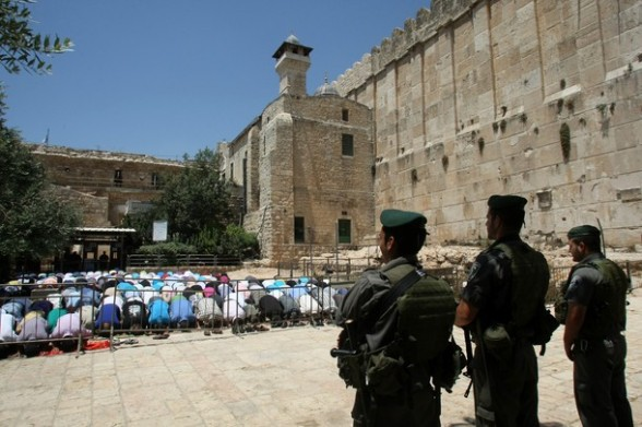 Israeli border policemen stand guard as Palestinian men perform the second Friday prayers of the Muslim fasting month of Ramadan outside the Ibrahimi Mosque or the Tomb of the Patriarchs in the West Bank city of Hebron on July 27, 2012. AFP PHOTO / HAZEM BADER
