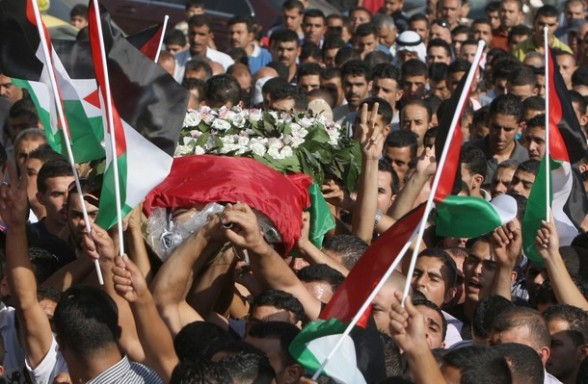 The body of 40-year-old Akram Dair is carried to his final burial place close to the West Bank city of Ramallah, after he was shot and killed by Israeli soldiers on July 31, 2012, at a checkpoint near East Jerusalem, Palestinian medical and security sources said. AFP PHOTO / ABBAS MOMANI