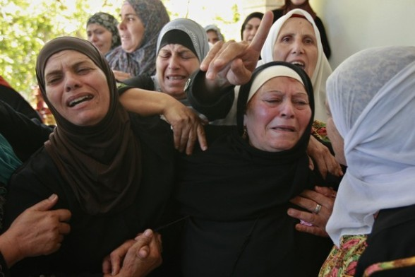 Palestinians womenmourn during the funeral of  Akram Badr, 46,  in the village of Beitillu near in the West Bank city of Ramallah,  Tuesday, July 31, 2012. Badr was killed at a checkpoint by the Israeli security forces near Jerusalem Monday. (AP Photo/Majdi Mohammed)