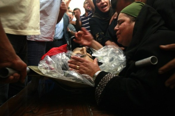 A Palestinian woman mourns over the dead of  Akram Badr, 46, during a funeral in the village of Beitillu near in the West Bank city of Ramallah,  Tuesday, July 31, 2012. Badr was killed at a checkpoint by the Israeli security forces near Jerusalem Monday. (AP Photo/Majdi Mohammed)