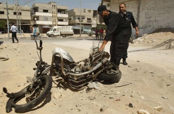 Palestinian Hamas policemen inspect the remains of motorcycle that was hit by an Israeli air strike in Rafah in the southern Gaza Strip August 5, 2012. An Israeli air strike killed a Palestinian resistance fighter and wounded another on Sunday as they rode a motorbike in southern Gaza, near the Egyptian border, hospital officials said. REUTERS/Ibraheem Abu Mustafa