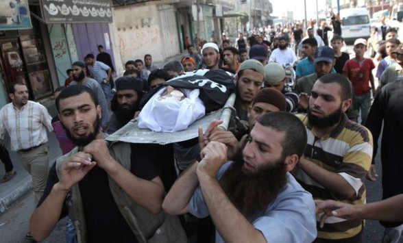 Palestinians carry the body of mujaheed Eid Hijazi, 23, during his funeral following an Israeli air strike on Rafah in the southern Gaza Strip, on August 5, 2012. An Israeli air strike killed a Palestinian resistance fighter and wounded another as they rode a motorbike in southern Gaza, hospital officials said. AFP PHOTO/ SAID KHATIB