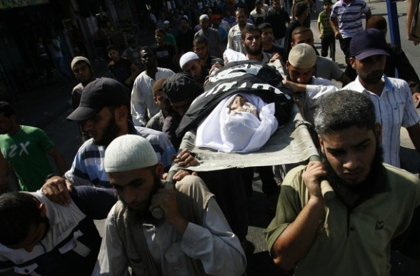 Mourners carry the body of a Palestinian mujaheed E'id Ucaal Hejazi during his funeral  in Rafah , southern Gaza Strip, Sunday, Aug. 5, 2012. Hejazi was killed on  an Israeli air strike Sunday and was a member of the Popular Resistance Committees, a resistance group, A Palestinian security official said. (AP Photo/Eyad Baba)
