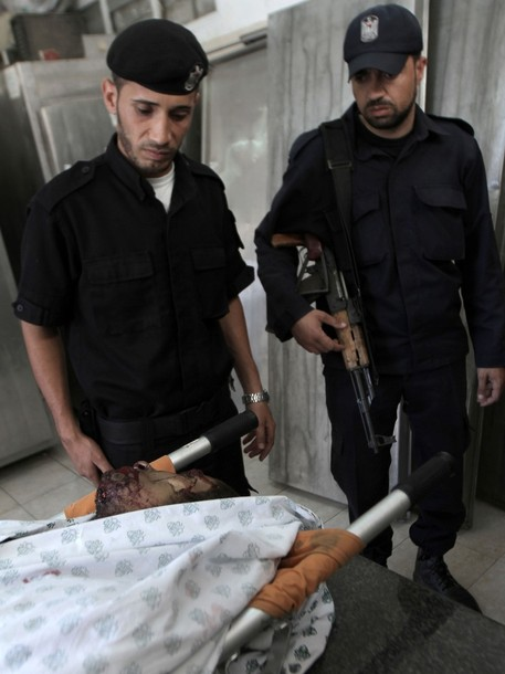 Palestinian police look at the body of Eid Hijazi, 23, brought into the al-Najar hospital following an Israeli air strike on Rafah in the southern Gaza Strip, on August 5, 2012. An Israeli air strike killed a Palestinian resistance fighter and wounded another as they rode a motorbike in southern Gaza, hospital officials said. AFP PHOTO/ SAID KHATIB