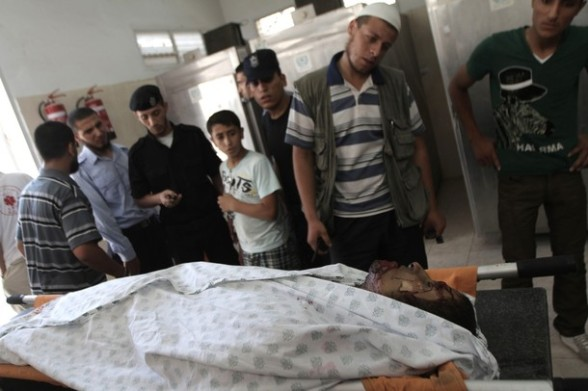 Palestinias look at the body of Eid Hijazi, 23, brought into the al-Najar hospital following an Israeli air strike on Rafah in the southern Gaza Strip, on August 5, 2012. An Israeli air strike killed a Palestinian resistance fighter and wounded another as they rode a motorbike in southern Gaza, hospital officials said. AFP PHOTO/ SAID KHATIB