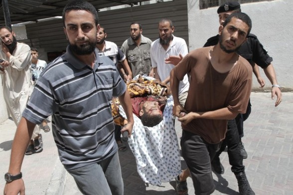Palestinians carry the body of  Eid Hijazi, 23,  into the al-Najar hospital following an Israeli air strike on Rafah in the southern Gaza Strip, on August 5, 2012. An Israeli air strike killed a Palestinianresistance fighter and wounded another as they rode a motorbike in southern Gaza, hospital officials said. AFP PHOTO/ SAID KHATIB