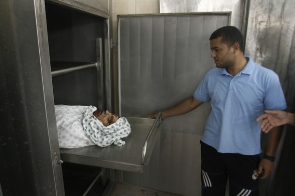 Palestinians  look at the body of 22-year-old E'id Ucaal Hejazi at the morgue in Rafah , southern Gaza Strip, Sunday, Aug. 5, 2012. Hejazi was killed on  an Israeli air strike Sunday and was a member of the Popular Resistance Committees, a resistance group, A Palestinian security official said.  (AP Photo/Eyad Baba)