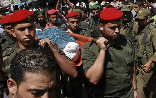 Palestinian security officers carry the body of Palestinian security official Anes Abu Al-Enan, during his funeral in Rafah Refugee Camp, southern Gaza Strip,Thursday, Sept. 20, 2012. Gaza's Hamas rulers say an Israeli airstrike on a vehicle in the southern Gaza Strip has killed two security personnel. Israel claimed Thursday that it had targeted two militants — one suspected of planning an attack on Israeli civilians and another accused of selling weapons.(AP Photo/Adel Hana)