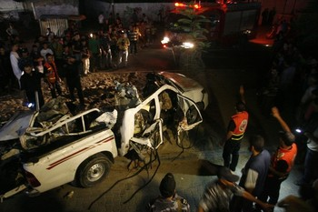 Palestinians inspect a destroyed vehicle following an Israeli air strike in Rafah southern Gaza Strip, Wednesday, Sept. 19, 2012. A Palestinian health official says an Israeli airstrike has killed two people in the southern Gaza Strip and another person was wounded. (AP Photo/Eyad Baba)