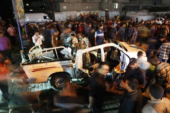 Palestinians gather around the wreckage of a car targeted by an Israeli aircraft in the town of Rafah in southern Gaza Strip on September 19, 2012. An Israeli air strike on the Gaza Strip killed two Palestinians and wounded one late on September 19, the Hamas-run emergency services said. AFP PHOTO / SAID KHATIB