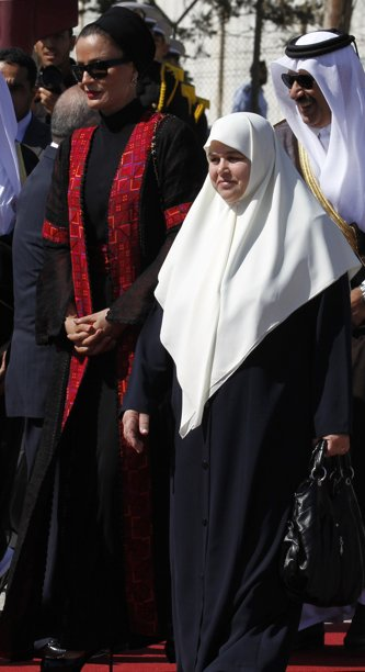 Sheikha Mozah Bint Nasser al Missned (L), wife of the Emir of Qatar Sheik Hamad bin Khalifa al-Thani, walks with Amal Haniyeh, wife of Hamas Prime Minister Ismail Haniyeh, during a welcoming ceremony at the Rafah border crossing with Egypt in southern Gaza October 23, 2012. The Emir of Qatar entered the Gaza Strip on Tuesday for a visit that broke the isolation of its Islamist rulers, Hamas, but disappointed Israel and mainstream Palestinian leaders in the West Bank. REUTERS/Mohammed Abed/Pool