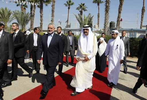 Hamas Prime Minister Ismail Haniyeh walks with the Emir of Qatar Sheik Hamad bin Khalifa al-Thani (front R) during a welcoming ceremony at the Rafah border crossing with Egypt in the southern Gaza Strip October 23, 2012. The Emir of Qatar entered the Gaza Strip on Tuesday for a visit that broke the isolation of its Islamist rulers, Hamas, but disappointed Israel and mainstream Palestinian leaders in the West Bank. REUTERS/Mohammed Abed/Pool