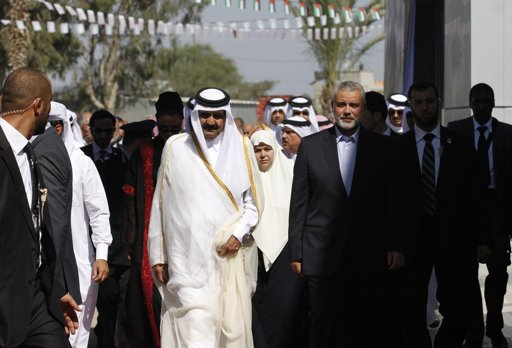 Hamas Prime Minister Ismail Haniyeh (front R) and his wife Amal (second row C) walk with the Emir of Qatar Sheik Hamad bin Khalifa al-Thani (front L) during a welcoming ceremony at the Rafah border crossing with Egypt in the southern Gaza Strip October 23, 2012. The Emir of Qatar entered the Gaza Strip on Tuesday for a visit that broke the isolation of its Islamist rulers, Hamas, but disappointed Israel and mainstream Palestinian leaders in the West Bank. REUTERS/Mohammed Abed/Pool