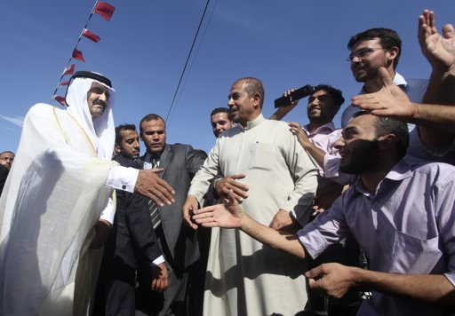 The Emir of Qatar Sheikh Hamad bin Khalifa al-Thani (L) is greeted by Palestinians upon his arrival to a cornerstone laying ceremony for a new center providing artificial limbs, in Beit Lahiya in the northern Gaza Strip October 23, 2012. The Emir of Qatar embraced the Hamas leadership of Gaza on Tuesday with an official visit breaking the isolation of the militant Palestinian Islamist movement, to the dismay of Israel and rival, Western-backed Palestinian leaders in the West Bank. REUTERS/Ali Ali/Pool