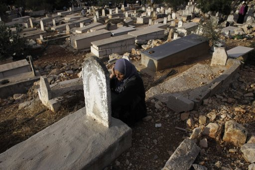 A Palestinian woman sits near a grave as she visits a cemetery on the first day of Eid al-Adha, in the West Bank city of Ramallah October 26, 2012. Muslims around the world celebrate Eid al-Adha to mark the end of the Haj by slaughtering sheep, goats, cows and camels to commemorate Prophet Abraham's willingness to sacrifice his son Ismail on God's command. REUTERS/Mohamad Torokman
