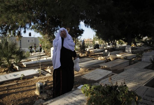 A Palestinian woman prays near a grave as she visits a cemetery on the first day of Eid al-Adha, in the West Bank city of Ramallah October 26, 2012. Muslims around the world celebrate Eid al-Adha to mark the end of the Haj by slaughtering sheep, goats, cows and camels to commemorate Prophet Abraham's willingness to sacrifice his son Ismail on God's command. REUTERS/Mohamad Torokman