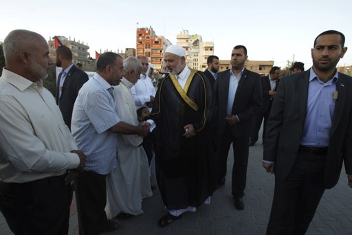 Hamas Prime Minister Ismail Haniyeh (C) greets people as he arrives for a special prayer on the first day of Eid al-Adha in the central Gaza Strip October 26, 2012. Muslims around the world celebrate Eid-al-Adha, marking the end of the haj, by slaughtering sheep, goats, cows and camels to commemorate Prophet Abraham's willingness to sacrifice his son Ismail on God's command. REUTERS/Ibraheem Abu Mustafa