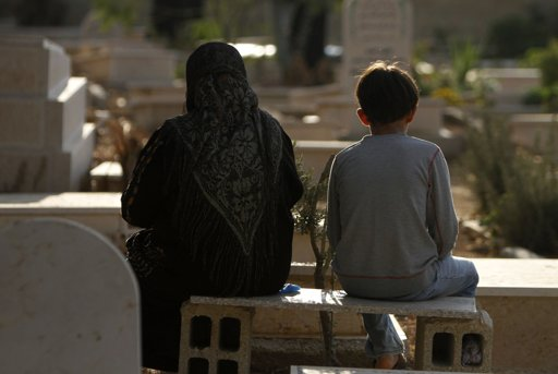 A Palestinian woman sits next to a boy as they visit a cemetery on the first day of Eid al-Adha, in the West Bank city of Ramallah October 26, 2012. Muslims around the world celebrate Eid al-Adha to mark the end of the Haj by slaughtering sheep, goats, cows and camels to commemorate Prophet Abraham's willingness to sacrifice his son Ismail on God's command. REUTERS/Mohamad Torokman