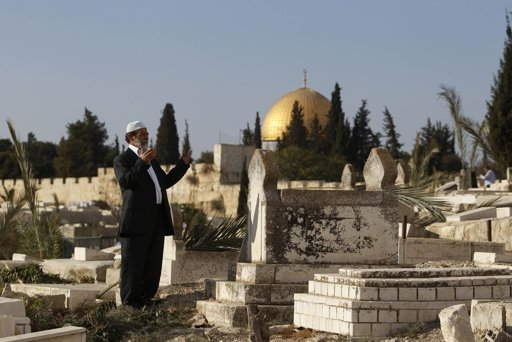 The Dome of the Rock is seen in the background as a Palestinian man prays on the first day of Eid al-Adha, at a cemetery in Jerusalem's Old City October 26, 2012. Muslims around the world celebrate Eid al-Adha to mark the end of the Haj by slaughtering sheep, goats, cows and camels to commemorate Prophet Abraham's willingness to sacrifice his son Ismail on God's command. REUTERS/Ammar Awad