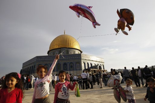 Palestinian girls hold balloons in front of the Dome of the Rock on the compound known to Muslims as al-Haram al-Sharif and to Jews as Temple Mount in Jerusalem's Old city, on the first day of Eid al-Adha October 26, 2012. Muslims around the world celebrate Eid al-Adha to mark the end of the Haj by slaughtering sheep, goats, cows and camels to commemorate Prophet Abraham's willingness to sacrifice his son Ismail on God's command. REUTERS/Ammar Awad