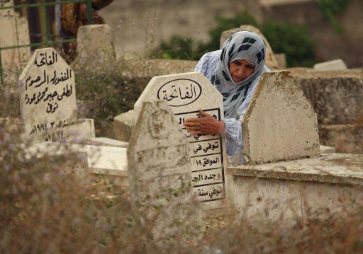 A Palestinian woman touches a tombstone as she visits a cemetery on the first day of Eid al-Adha, in the West Bank village of Deir al Hatab near Nablus October 26, 2012. Muslims around the world celebrate Eid al-Adha to mark the end of the Haj by slaughtering sheep, goats, cows and camels to commemorate Prophet Abraham's willingness to sacrifice his son Ismail on God's command. REUTERS/Abed Omar Qusin