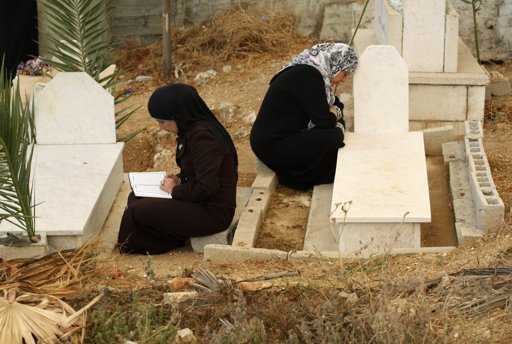 Palestinian women pray near graves as they visit a cemetery on the first day of Eid al-Adha, in the West Bank village of Deir al Hatab near Nablus October 26, 2012. Muslims around the world celebrate Eid al-Adha to mark the end of the Haj by slaughtering sheep, goats, cows and camels to commemorate Prophet Abraham's willingness to sacrifice his son Ismail on God's command. REUTERS/Abed Omar Qusin