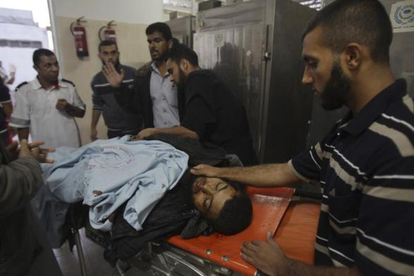 Palestinians surround the body of a militant at a hospital morgue in Rafah in the southern Gaza Strip October 24, 2012. Israel killed three Hamas gunmen in Gaza Strip air strikes on Tuesday which the military said targeted squads preparing to launch rockets into the Jewish state. REUTERS/Ibraheem Abu Mustafa