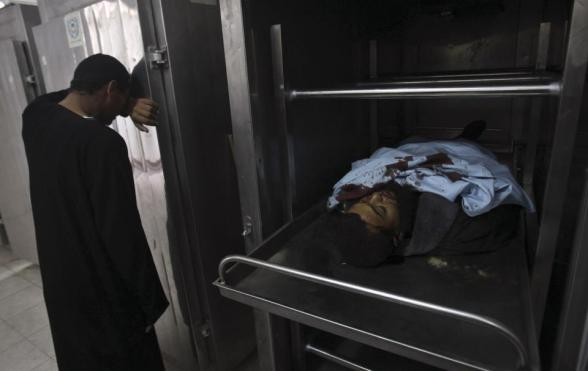 A Palestinian man reacts as the body of a Palestinian militant is shown to the media at a hospital morgue in Rafah in the southern Gaza Strip October 24, 2012 . Israel killed one Hamas gunman in its second round of air strikes in as many days on the Gaza Strip on Wednesday, responding to rocket fire at its southern towns that wounded three people. Separate raids by Israel on Tuesday killed three Hamas gunmen Tuesday which the military said targeted squads preparing to launch rockets into the Jewish state. REUTERS/Ibraheem Abu Mustafa
