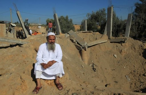 A Palestinian man sits on th edge of a crater following an Israeli attack which damaged a building in al-Bureij in the center of the Gaza Strip on October 29, 2012. Gaza resistance fighters on Monday fired 18 rockets at southern Israel, ending several days of calm, with the armed wing of the ruling Hamas movement saying it was revenge after an air raid killed one of their men