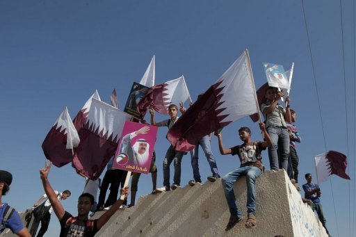 Palestinian youths wave the Qatari flag near the Rafah border crossing with Egypt prior to the arrival of Qatari Emir Sheikh Hamad bin Khalifa al-Thani to the Gaza Strip on October 23. The emir arrived in Gaza on Tuesday in the first visit by a head of state since the Islamist Hamas movement took over in 2007