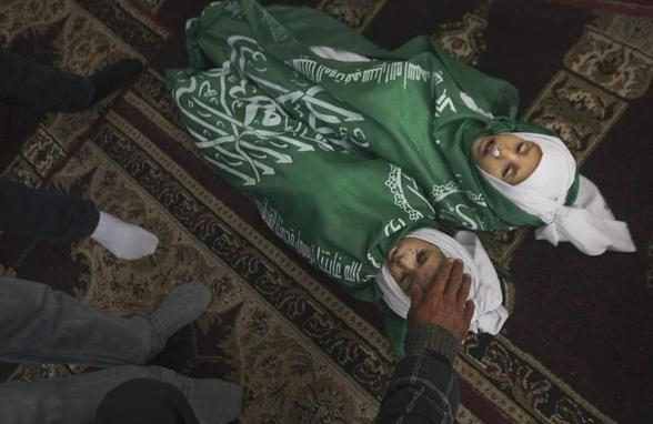 "A Palestinian boy stands next to the bodies of Jumana Abu Sefan, 18 months old, and her brother Tamer, three and a half years old, during their funeral at a mosque in the northern Gaza Strip November 18, 2012. The two siblings were killed in an Israeli air strike on Sunday, hospital officials said. Israel bombed dozens of targets in Gaza for a fifth straight day on Sunday, launching aerial and naval attacks as its military prepared for a possible ground invasion, though Egypt saw ""some indications"" of a truce ahead. REUTERS/Mohammed Salem"