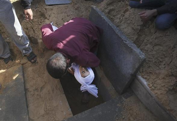 AA02. Gaza Strip (---), 18/11/2012.- A man buries a Palestinian child from the Abu Sefan family at a cemetery in the northern Gaza Strip on 18 November 2012. Reports state that the Israeli military is prepared to significantly widen operations against Palestinian militants in the Gaza Strip, Prime Minister Benjamin Netanyahu told his cabinet 18 November 2012. He said Israel's Operation Pillar of Defence had caused 'significant damage' to the missile arsenal that Palestinian militant groups were aiming at Israel, and had extracted a 'heavy price' from Hamas and other armed organizations. EFE/EPA/ALI ALI