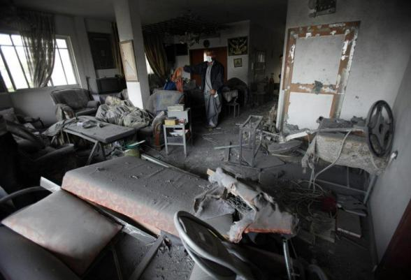 A Palestinian inspects his damaged house after an Israeli air strike in Gaza City November 17, 2012. Israeli aircraft pounded Hamas government buildings in Gaza on Saturday, including the building housing the prime minister's office, after Israel's Cabinet authorised the mobilisation of up to 75,000 reservists, preparing the ground for a possible invasion into Gaza. REUTERS/Suhaib Salem