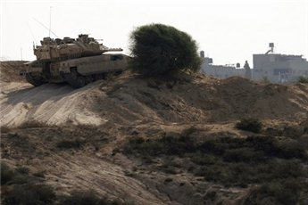 An Israeli tank patrols just outside the border with the northern 