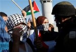 Palestinian protesters shout slogans in front of Israeli soldiers during a