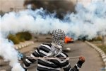 A stone-thrower uses a sling to throw back a tear gas canister fired