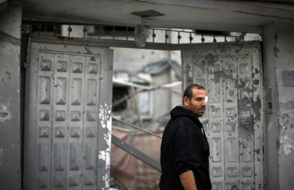 A wounded Palestinian stands outside his damaged house after an Israeli air strike in Gaza City November 17, 2012. Israeli aircraft pounded Hamas government buildings in Gaza on Saturday, including the building housing the prime minister's office, after Israel's Cabinet authorised the mobilisation of up to 75,000 reservists, preparing the ground for a possible invasion into Gaza. REUTERS/Suhaib Salem