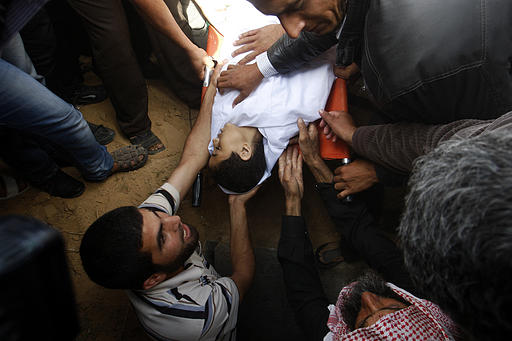 People bury Ahmed Abu-Daqa, 11, in Khan Younis, southern Gaza Strip, Sunday, Oct. 28, 2012. It was not clear who shot the boy. Palestinian militants and Israeli forces were exchanging fire at the time when the boy was killed Thursday evening. Photo by AP